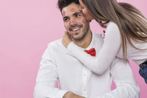 young-woman-kissing-man-with-lipstick-kiss-marks-cheek